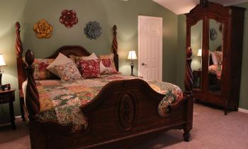 The four-poster bed and antique armoire just add to the warm atmosphere.